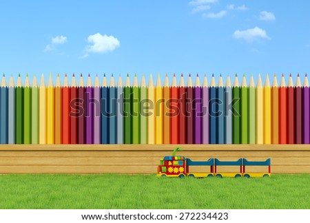Garden for children with toy train on the grass and fence with colorful pencils - 3D Rendering - stock photo