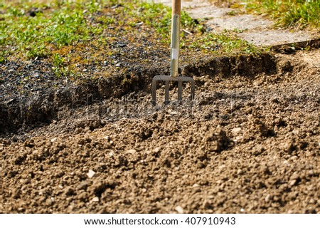 Garden fork pitched in soil, symbolizing garden work, gardening and planting preparation. Housework, self-supply, food production, having a break from work concept.  - stock photo