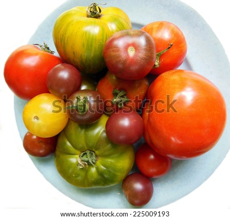 Garden fresh collection of heirloom tomatoes of different sizes on blue plate and white background - stock photo
