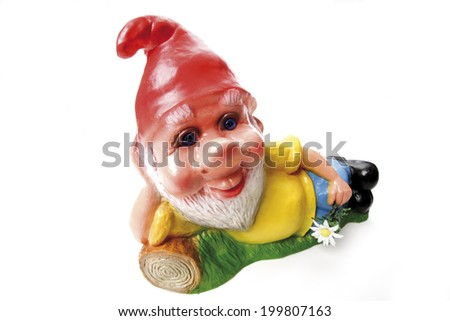 Garden gnome lying on meadow - stock photo
