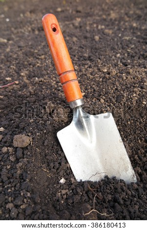 Garden hand trowel in the loosen soil in the garden - stock photo