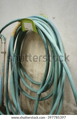 Garden hose for watering plants at the park. - stock photo