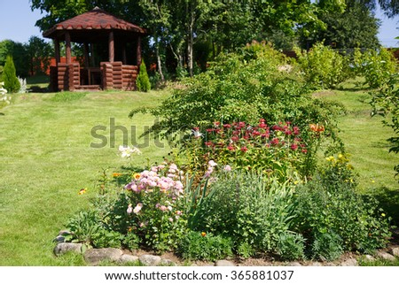 Garden in the summer clear day with flower beds and a gazebo - stock photo