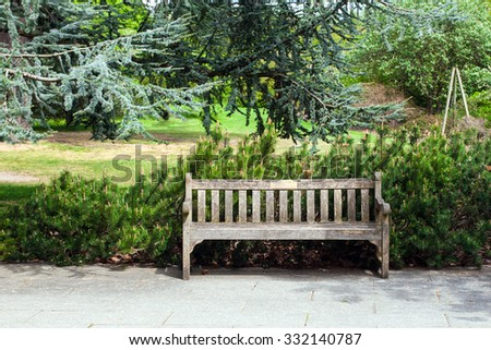 Garden landscape with a bench - stock photo