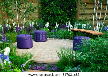 Garden landscape with a bench and seats - stock photo