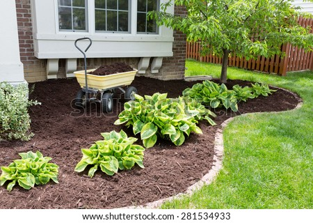 Garden maintenance in spring doing the mulching of the flowerbeds to keep down weeds and retain moisture in the soil - stock photo