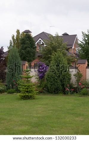 garden of a private home which is behind the tress - stock photo