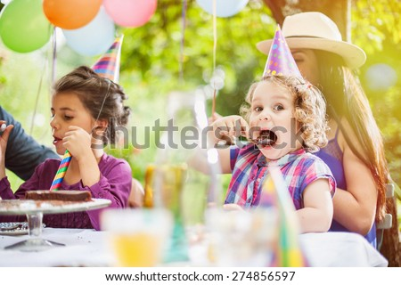 Garden party family sharing the birthday cake. The three year old is enjoying her piece, the garden is decorated with balloons and colors are bright - stock photo