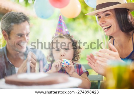 garden party with family for little girl's birthday, girl blowing out the candles on the cake, the garden is decorated with balloons and colors are bright - stock photo