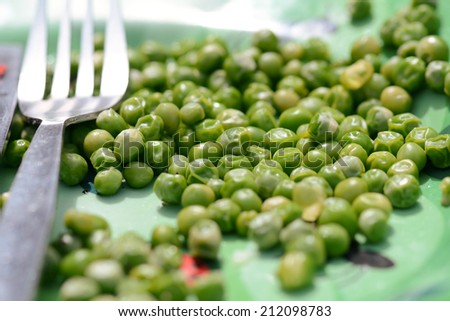 Garden peas left on plate - stock photo
