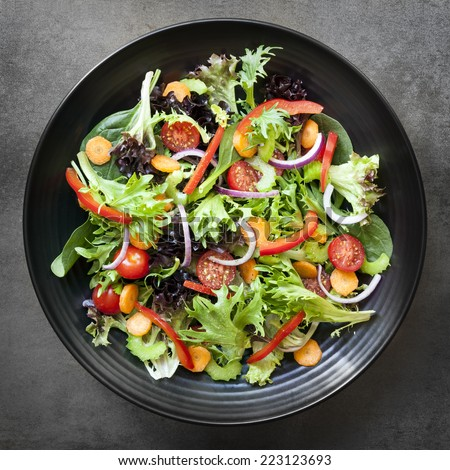 Garden salad in black bowl.  Overhead view. - stock photo