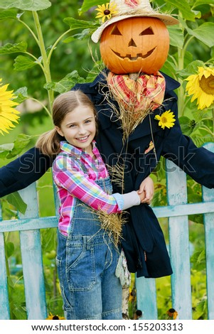 Garden, Scarecrow and happy girl  in the garden - Autumn harvests - stock photo