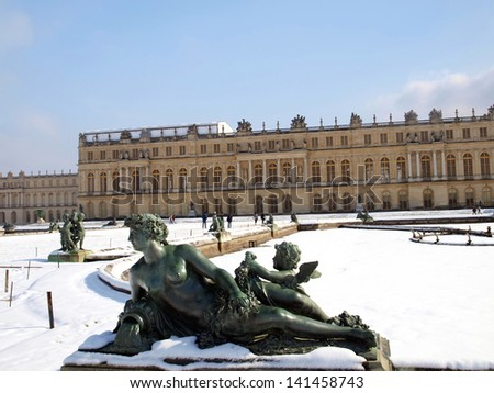 garden sculptures and pond in front of the royal residence at Versailles near Paris in France in winter scenery, the snow - stock photo
