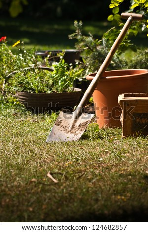 Garden shovel with pots and plants in the background - stock photo