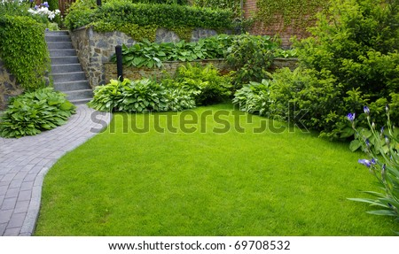 Garden stone path with grass growing up between the stones - stock photo