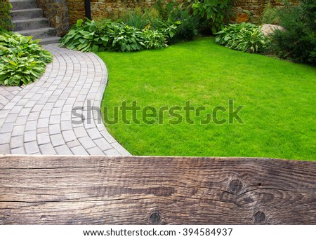 Garden stone path with grass growing up between the stones. Wooden background for text. - stock photo