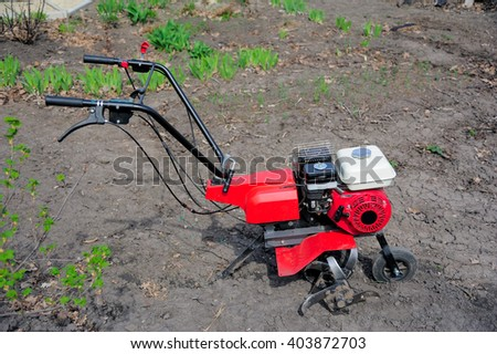 Garden tiller in the field - stock photo