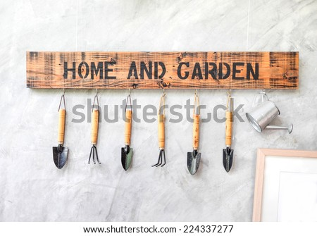 Garden tool hanging on concrete wall with wooden label - stock photo