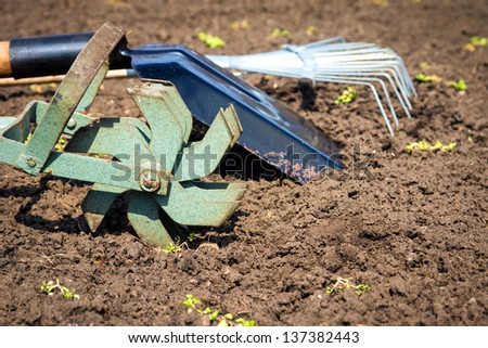 Garden tools (cultivator, shovel, rake) over brown soil (ploughed land) close up. Copy space. Agriculture, gardening, soil cultivation concept. - stock photo