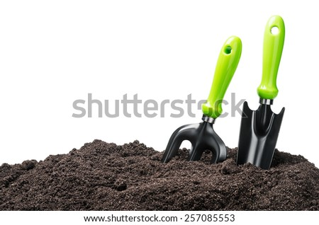 garden tools in soil isolated on white background - stock photo