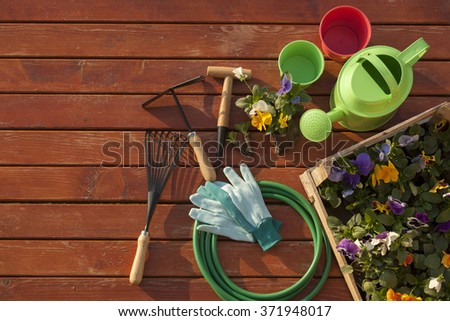 Garden tools on grass in yard - stock photo