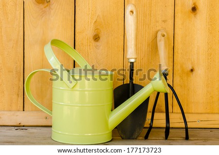 Garden tools with watering can, trowel, and hand cultivator on wood background. - stock photo