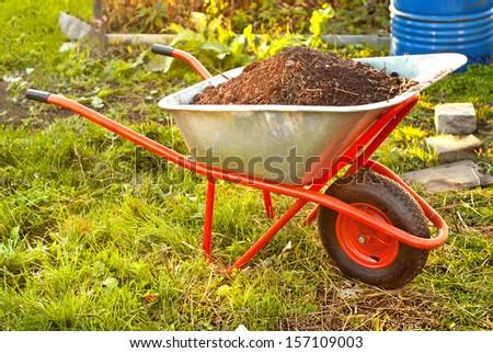 Garden wheelbarrow full of humus soil - stock photo