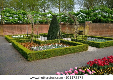 Garden with small bushes, white, orange and red tulips and brick walls in Keukenhof park in Holland - stock photo