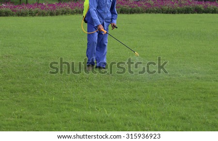 Gardener is spraying of insecticides at lawn  - stock photo