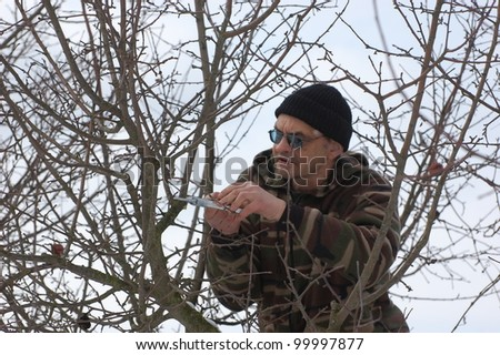 Gardener pruning the branches of apple tree in early spring. Near Kiev,Ukraine - stock photo