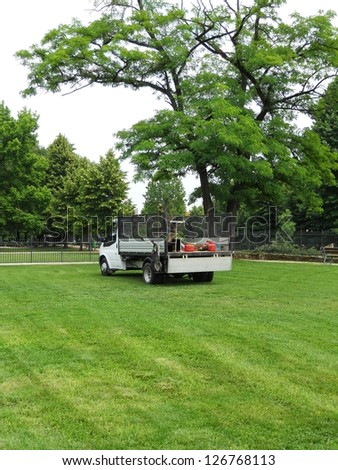 Gardener's truck and equipment on freshly cut grass - stock photo