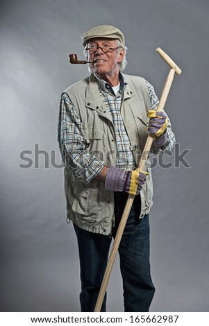 Gardener senior man with hat holding hoe. Wearing glasses and smoking pipe. Studio shot against grey. - stock photo