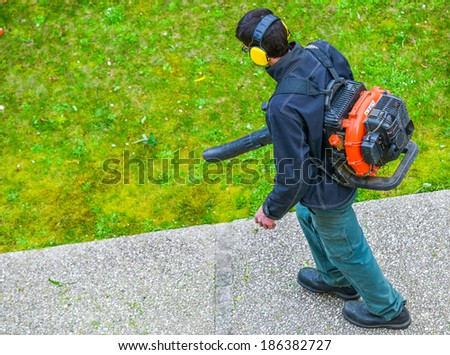 gardener using a gas blower in a park - stock photo