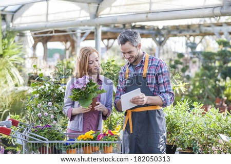 gardener using his digital tablet to advise a female client who buys flowers - stock photo