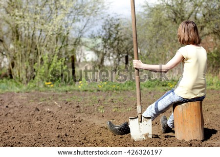 gardener with long shovel in his hand, resting on a tree stump in the background digging up the garden / gardener resting after a hard day's work - stock photo
