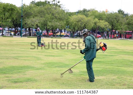 gardeners on a field cutting grass by lawnmower - stock photo