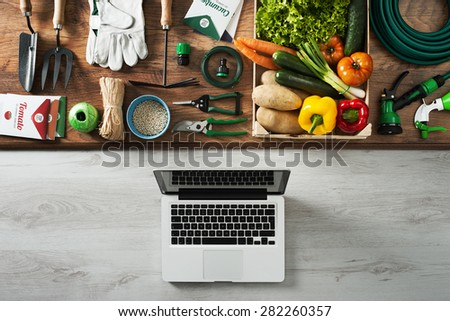 Gardening and farming tools on a wooden table and laptop, top view - stock photo