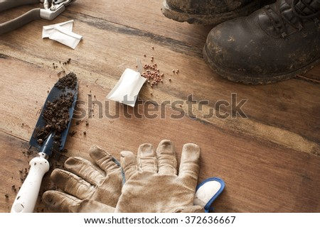 Gardening background concept with gloves , old boots and a trowel with scattered soil on a wooden surface with copy space, high angle view - stock photo