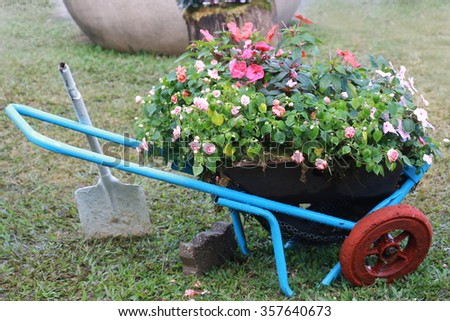 gardening cart with flower pot in flower garden, wheelbarrow full of dried leaves, gardening with shovel tool. - stock photo