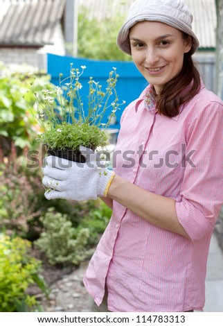 Gardening concept - woman with flowers in the garden - stock photo