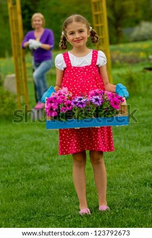 Gardening, flower garden, planting concept - lovely gardener working with mother in the garden - stock photo