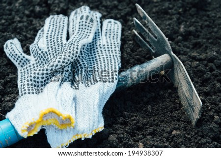 Gardening hoe and gloves on land - stock photo