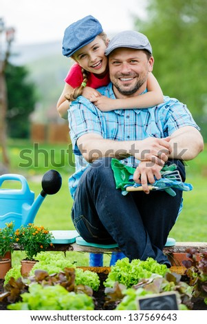Gardening, planting, cultivation - young girl with father working in vegetable garden - stock photo