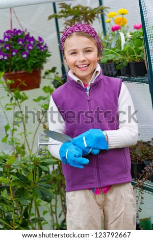 Gardening, planting - lovely girl  in the greenhouse - stock photo