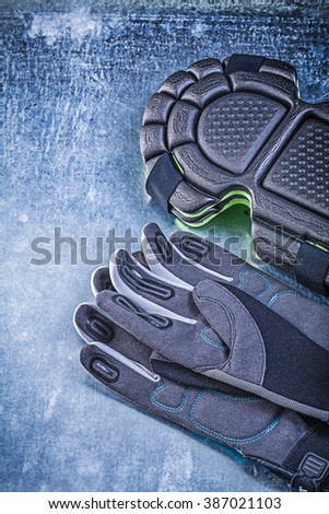 Gardening protective gloves knee pads on metallic background agriculture concept. - stock photo