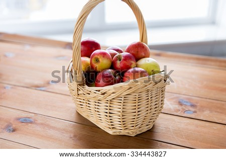 gardening, season, autumn and fruits concept - close up of wicker basket with ripe red apples on wooden table - stock photo