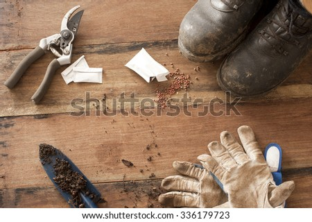 Gardening still life with old boots, secateurs, trowel and gloves displayed in the corners on a rustic wood background - stock photo