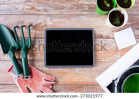 gardening, technology and planting concept - close up of tablet pc computer blank screen, seedlings, seeds and garden tools on table - stock photo