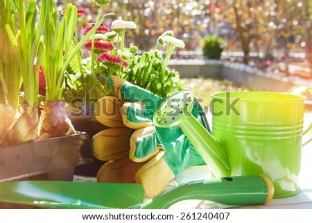 Gardening tools and a straw hat on the grass in the garden - stock photo