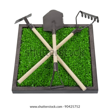 Gardening tools on a bed of raised green grass - path included - stock photo
